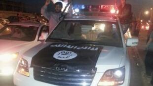 Des combattants du groupe EI célèbrent leur victoire à Mossoul, sur un véhicule pris à la police irakienne, le 23 juin 2014.