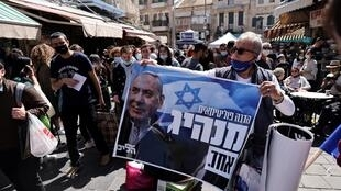 À Mahane Yehuda, partisan de Benyamin Netanyahu brandissant une affiche du Premier Ministre.