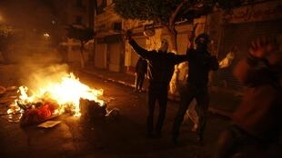 Algerian protesters hold knives during clashes with police in Bab el-Oued district of Algiers