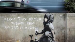 «A partir de maintenant, le désespoir prend fin et la tactique commence», est-il écrit en grandes lettres blanches à côté de l'enfant portant un foulard. Cette peinture murale dans le centre de Londres est attribuée à Bansky.