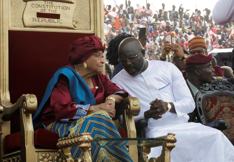 O novo Presidente da Lbéria, George Weah, em companhia da Presidente cessante, Ellen Johnson Sirleaf, durante a cerimónia de tomada de posse - 22 de Janeiro de 2018