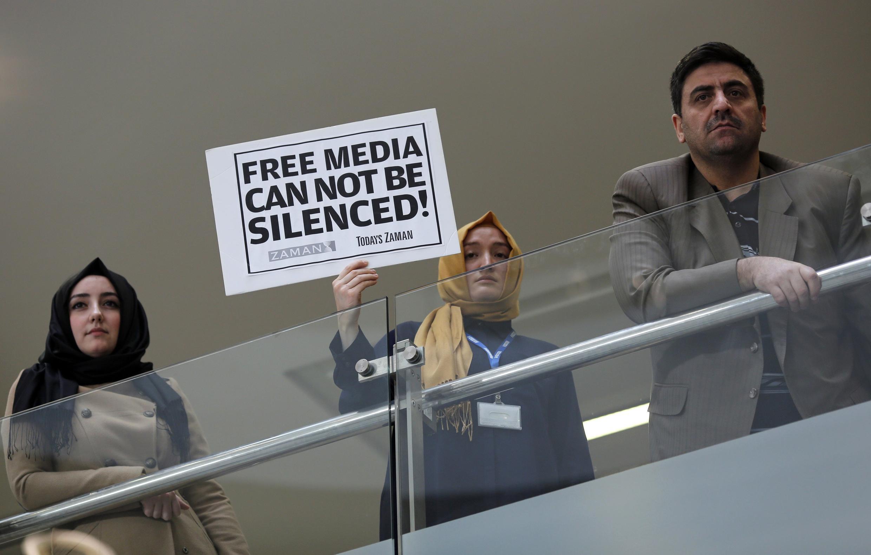 Une journaliste tient une pancarte où l'on peut lire: «Un média libre ne peut rester silencieux», au siège du journal «Zaman», dimanche 14 décembre 2014.
