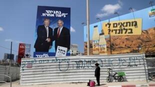 Un ultra-orthodoxe devant une affiche du Likoud montrant le Premier ministre Benjamin Netanyahu et Donald Trump.