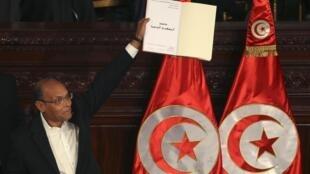 Le président tunisien, Moncef Marzouki, tenant la nouvelle constitution adoptée le 27 janvier 2014. Le texte consacre l'indépendance de la justice par rapport au pouvoir exécutif.