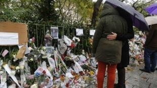 Personas rinden un homenaje a las víctimas de los atentados de París, frente al Bataclan.