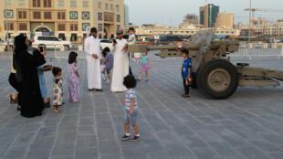 """Famílias tiram fotos em frente do """"canhão do Ramadã"""", que anuncia a quebra diária do jejum, em Doha, capital do Catar."""