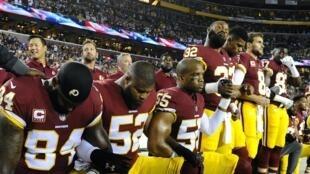 Des membres de l'équipe du Washington Redskins posent un genou à terre et baissent la tête pendant  l'hymne américain, le 24 septembre 2017.