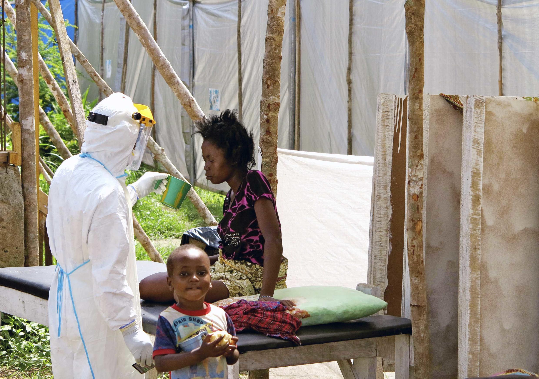 Un agent de santé, vêtu d'une combinaison de protection, offre de l'eau à une femme atteinte de la maladie d'Ebola, dans un centre de traitement pour les personnes infectées à l'hôpital public de Kenema en Sierra Leone en août 2014.
