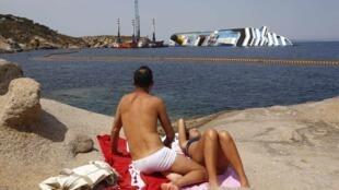 O navio Costa Concordia continua no local onde naufragou, na Itália, em pleno verão europeu.
