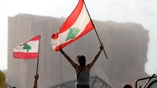 Des manifestants s'affichent avec des drapeaux du Liban, lors de manifestations près du site de l'explosion à Beyrouth, le 11 août 2020.