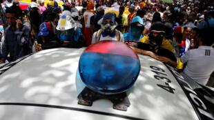 Des manifestants autour d'un véhicule de patrouille dans une rue de Caracas, le 27 juin 2017.
