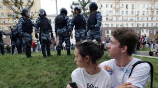 A Moscou, ce couple se tient non loin des forces de l'ordre lors des manifestations du 12 juin.