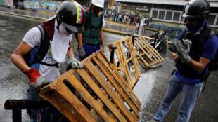 Des manifestants préparent des barricades à Caracas à la veille de la grève nationale, le 19 juillet 2017.