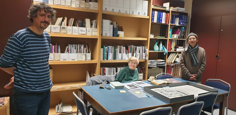 Họa sĩ Vink (P) và ông Fabien Denoël (T), phụ trách khoa học của Quỹ Di Sản thành phố Liège (Fonds patrimoniaux de la Ville de Liège) chụp ảnh với bà Isabelle Zumkir, tình nguyện viên, nhập kho 173 bản vẽ Vink tặng thành phố.