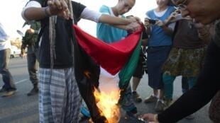 Des colons israéliens brûlent un drapeau palestinien dans la colonie de Beit El, le 20 septembre 2011.