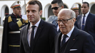 Tunisian President Beji Caid Essebsi (R) welcomes French President Emmanuel Macron (C) following his arrival at Presidential Palace in Carthage on Wednesday