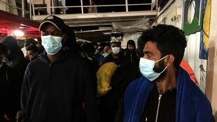 Des migrants, portant des masques de protection anti-Covid, se préparent à débarquer dans le port sicilien de Porto Empedocle, le soir du 6 juillet 2020.