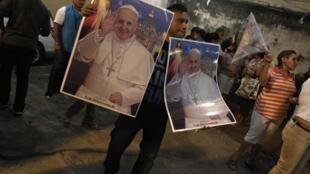 Vente de posters à l'effigie du pape François dans les taudis de Rocinha, à Rio de Janeiro, le 18 juillet 2013.
