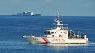 Un navire garde-côtes philippin navigue non loin d'un homologue chinois, en plein exercice conjoint avec les États-Unis près du récif de Scarborough, le 14 mai 2019.