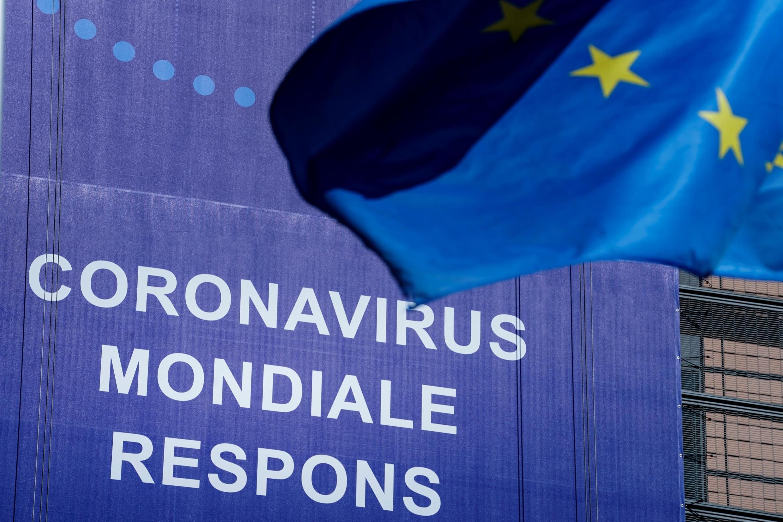 """Un drapeau de l'Union européenne (UE) flotte devant une bannière nouvellement accrochée qui lit """"Coronavirus Global Response"""" devant le bâtiment de la Commission européenne à Bruxelles, le 6 mai 2020."""