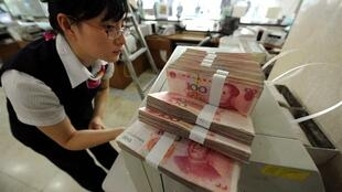 An employee stands next to stacks of yuan banknotes at a Bank of China branch in Hefei, Anhui province.