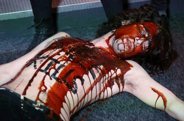 """Ativista com tinta cor de sangue e a inscrição """"A Shell mata"""", durante Salão do Automóvel de Bruxelas"""
