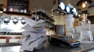 Uno tíquets y un datáfono de tarjeta de crédito, fotografiados el 28 de mayo de 2020 sobre la barra de un restaurante cerrado de París