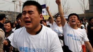 Hàng chục thân nhân các hành khách trên chuyến bay của Malaysia Airlines MH370 mất tích, biểu tình trước Đại sứ quán Malaysia ở Bắc Kinh, 25/03/2014.