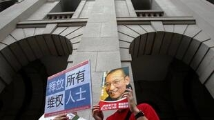 Protesters hold up placards with images of jailed Chinese democracy activist Liu Xiaobo during a demonstration in Hong Kong