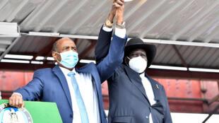 El jefe del Consejo Soberano de Sudán, Abdel Fattah al-Burhan (izq.) y el presidente de Sudán del Sur, Salva Kiir, se dan la mano al llegar a la firma del acuerdo de paz en Juba, el 3 de octubre de 2020.