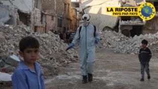Un casque blanc désinfecte un quartier détruit avant que le voisinage ne se réunisse pour rompre le jeûne à la tombée de la nuit en cette période de ramadan, le 7 mai 2020 à Atareb, dans la région d'Alep.