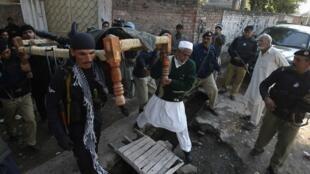 Les forces de sécurité pakistanaises aidées par un civil transportent le corps de l'un des leurs tué dans les affrontements de ce dimanche 16 décembre à Peshawar.