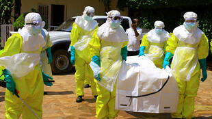 Protected paramedical workers take away the body of an Ebola victim.