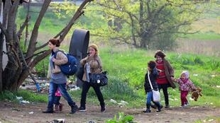 Migrantes sírios caminham na área de trânsito e retenção instituída pelo governo húngaro na fronteira com a Sérvia, onde a maioria dos imigrantes retidos são mulheres e crianças, segundo a ONG Helsinki Group.