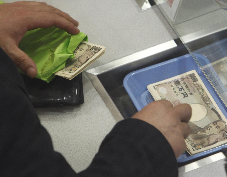 Một người Nhật đem Yên đổi lấy Đô la tại một điểm đổi tiền tại Tokyo ngày 16/09/2010