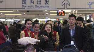 Ursula Gauthier (L), the Beijing-based correspondent for French news magazine L'Obs, speaks with hostesses at the airport before she takes her flight back to France, in Beijing on December 31, 2015.
