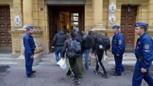 Des migrants sont escortés par des policiers hongrois au tribunal de Szeged, en octobre 2015 pendant le procès de migrants.