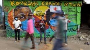 Des artistes de Mathare Roots Youth Organisation posent devant leur peinture murale prônant des pratiques de sécurité pour freiner la propagation du nouveau coronavirus, alors que les gens passent devant le bidonville de Mathare, le 29 avril 2020.