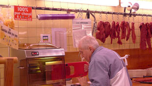 Butcher Jacques Leban mincing horsemeat at his shop in Paris.