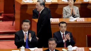 ប្រធានាធិបតីចិន លោកស៊ី ជីនពីង(ឆ្វេង) និងនាយករដ្ឋមន្រ្តីលី ខឺឆាំង(ស្តាំ) ទះដៃ នៅពេលលោកយូ ចេងស្ហេង Yu Zhengsheng ប្រធានសន្និសីទ the Chinese People's Political Consultative Conference (CPPCC)ឡើងថ្លែងសុន្ទរកថា នៅថ្ងៃសៅរ៍ទី៣មីនា ២០១៨