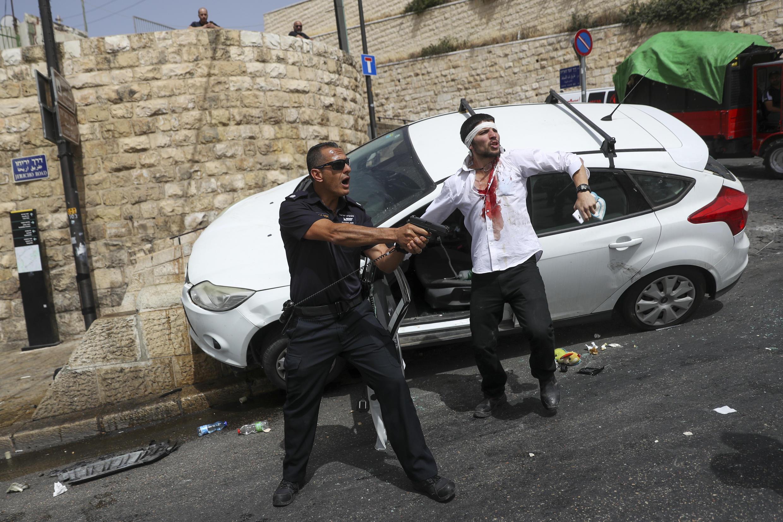 Un policía israelí protege a un conductor judío que fue atacado por manifestantes palestinos a quienes luego atropelló, cerca de la Ciudad Vieja de Jerusalén, el lunes 10 de mayo de 2021.