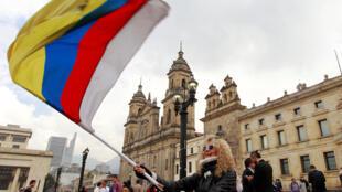 La bandera de Colombia con una franja más, blanca, símbolo de la paz.