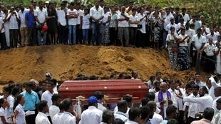 Sri Lankans carry a casket during a mass for victims in Negombo.