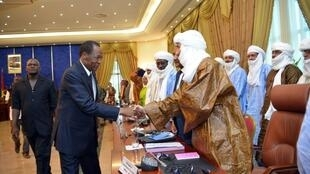 Burkina Faso's President Balise Compaore (C) greets MNLA general secretary Bilal ag Acherid, after signing their accord.