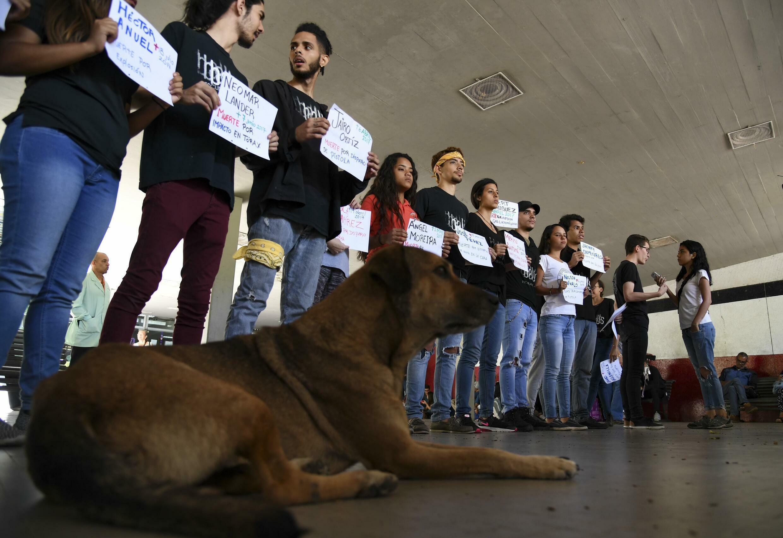 Estudiantes universitarios sostienen carteles con los nombres de compañeros de clase que murieron durante las protestas antigubernamentales en 2017 en el marco de una manifestación convocada por estudiantes de la Universidad Central de Venezuela (UCV) en Caracas, Venezuela, el 2 de mayo de 2019.