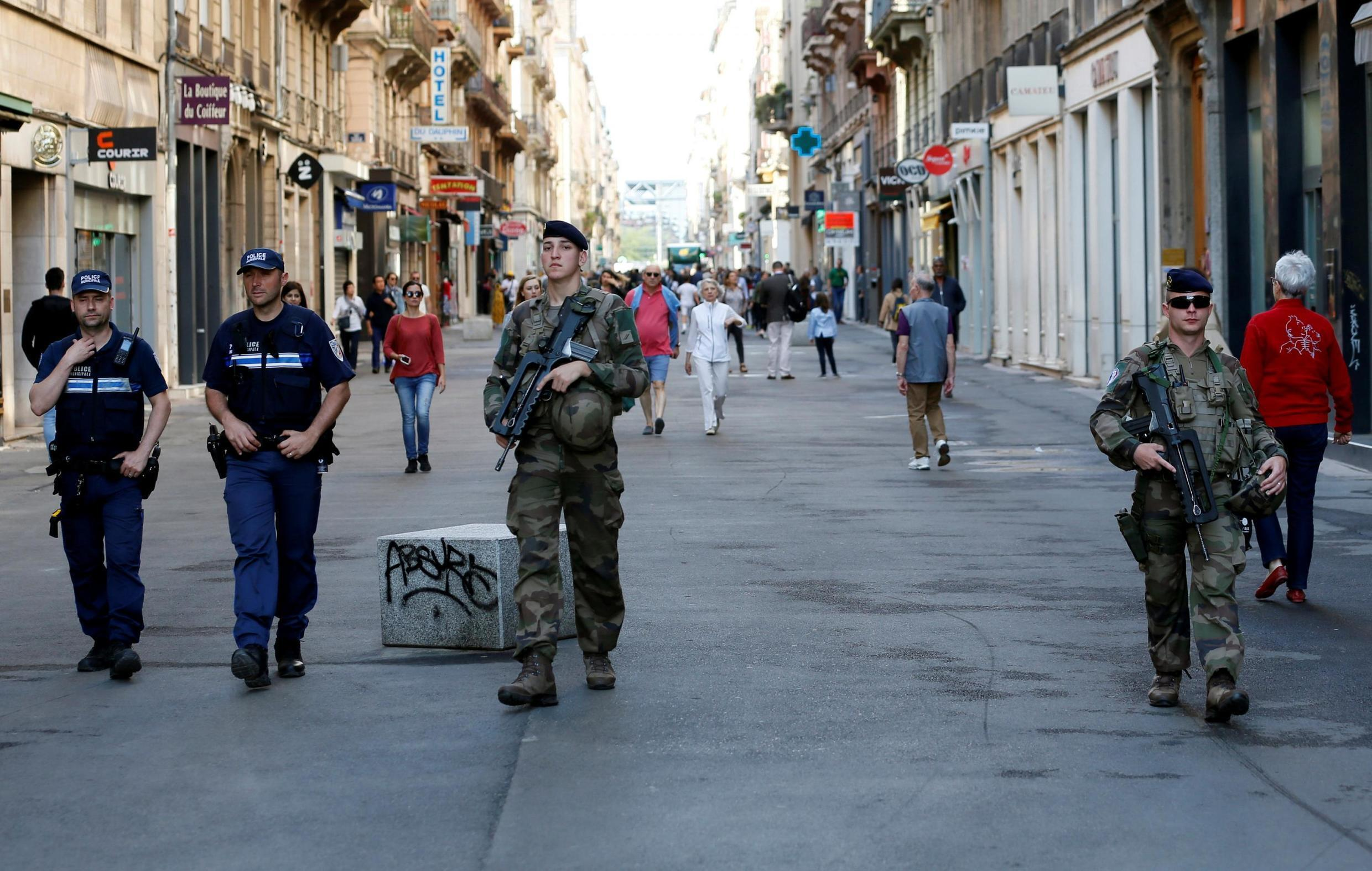 Police and army patrol the streets during the manhunt of a suspected suitcase bomber in central Lyon, France, 25 May 2019.