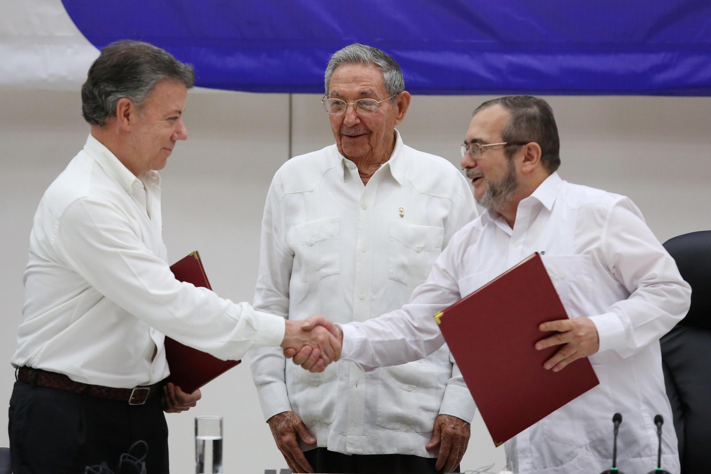 O presidente colombiano, Juan Manuel Santos (esquerda) e o líder das Farc, Timoleon Jimenez, selam acordo diante do presidente cubano, Raúl Castro.