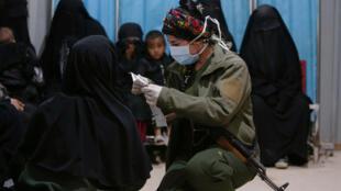 Una combatiente de las Fuerzas Democráticas Sirias (FDS) revisa los documentos de la esposa de un miembro del grupo Estado Islámico en la clínica del campamento de desplazados de Al-Hol, provincia de Hasaka, Siria. 2 de abril de 2019.