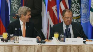 Ngoại trưởng Mỹ John Kerry (T) trao đổi với đồng nhiệm Nga Sergey Lavrov trước cuộc họp về Syria tại khách sạn ở New York, 18/12/2015