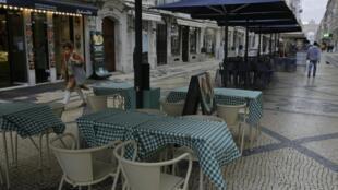 Des gens passent devant des terrasses de restaurants vides dans les rues de Lisbonne le 4 novembre 2020.